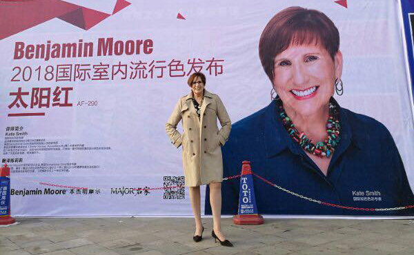 Kate Smith standing in front of china Benjamin Moore event billboard